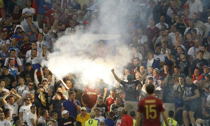 Flares are lit on the stands after Russia scored a goal during the Euro 2016 Group B soccer match between England and Russia, at the Velodrome stadium in Marseille, France, Saturday, June 11, 2016. (AP Photo/Kirsty Wigglesworth)