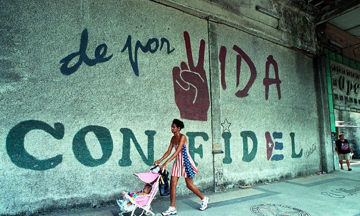 """A woman dressed in the colors of the United States flag pushes her baby as they walk past a wall that reads, """"A Lifetime with Fidel,"""" June 11, 2001 in Havana, Cuba. (Jorge Rey/Getty Images)"""
