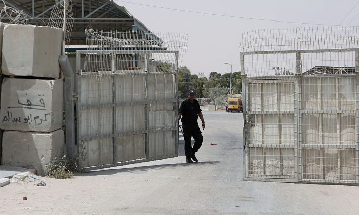 A Palestinian security officer closes the gate under Palestinian control at the Kerem Shalom crossing between Israel and the southern Gaza Strip, south of Rafah on June 7, 2015 after Israel closed, until further notice, the Erez crossing for people and the Kerem Shalom crossing for goods as Gaza militants resumed their rocket fire on southern Israel after warplanes blitzed the coastal enclave. AFP PHOTO / SAID KHATIB        (Photo credit should read SAID KHATIB/AFP/Getty Images)