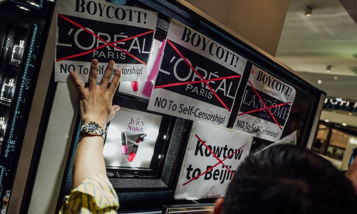 Protesters hold placards and shout slogans as they take part in a rally against French cosmetics brand Lancome at the store front of Lancome cosmetics in Causeway Bay, Hong Kong, on on June 8, 2016. (Anthony Kwan/Getty Images)