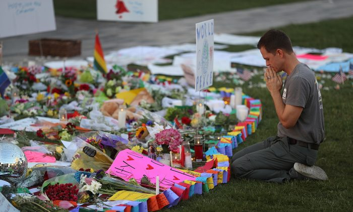 Matt Mitchell pays his respects to the Orlando shooting victims at a memorial in front the Dr. Phillips Center for the Performing Arts on June 14, 2016. (Joe Raedle/Getty Images)
