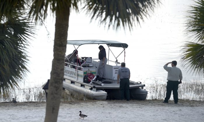 Law enforcement officials search the Seven Seas Lagoon outside the Grand Floridian Resort & Spa on Wednesday, June 15, 2016, in Lake Buena Vista, Fla., after a two-year-old toddler was dragged into the lake by an alligator. (AP Photo/Phelan M. Ebenhack)