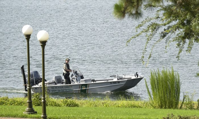 A law enforcement officer searches the Seven Seas Lagoon outside the Grand Floridian Resort & Spa on Wednesday, June 15, 2016, in Lake Buena Vista, Fla., after a two-year-old toddler was dragged into the lake by an alligator. (AP Photo/Phelan M. Ebenhack)