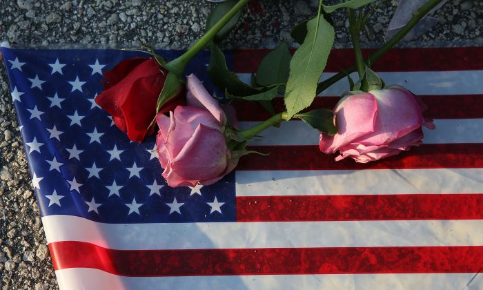 Flowers and an American flag are seen on the ground near the Pulse Nightclub where Omar Mateen allegedly killed at least 50 people on June 13, 2016 in Orlando, Florida. The mass shooting killed at least 50 people and injuring 53 others in what is the deadliest mass shooting in the country's history.  (Photo by Joe Raedle/Getty Images)