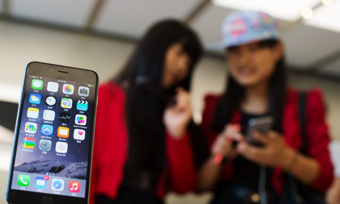 Chinese girls check out the iPhone 6 in an Apple store in Shanghai on October 17, 2014. ( Johannes Eisele/AFP/Getty Images)