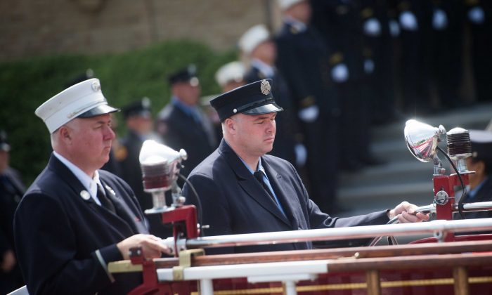 Firefighters Lt. Michael Stack (white hat) and Brian Stack (dark hat) ride on the back of the fire truck during the funeral of their father Fire Department of New York Battalion Chief Lawrence Stack who was  killed in the World Trade Center terror attacks of September 11, 2001, outside Saints Philip and James Roman Catholic Church June 17, 2016 in St James, New York. (Andrew Theodorakis/Getty Images)