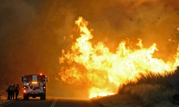Firefighters from the Lompoc City Fire Department take shelter behind their engine Thursday, June 16, 2016, as wind driven flames advance from the Sherpa Fire.  The flames were crossing Calle Real near El Capitan State Park in Santa Barbara County. (Mike Eliason/Santa Barbara County Fire Department via AP)