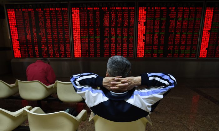 An investor watches stock price movements at a securities company in Beijing on June 15. (Greg Baker/AFP/Getty Images)