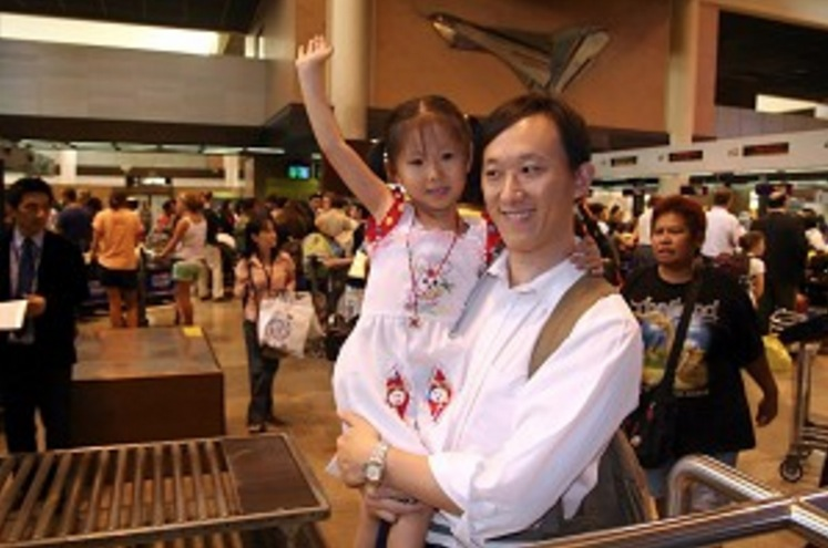 DON MUANG AIRPORT, BANGKOK: Huang Guohua and his 4-year-old daughter Huang Ying enjoy a happy moment while preparing to board a flight to New Zealand where they are being resettled, on January 15, 2006. (The Epoch Times)