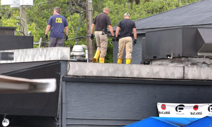 FBI lab personnel walk on the roof of the Pulse Nightclub Monday, June 20, 2016, investigating the mass shooting scene in Orlando. (Red Huber/Orlando Sentinel via AP)