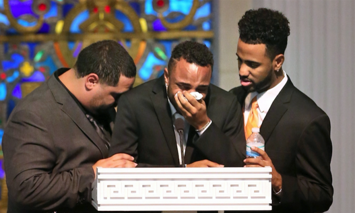 Sons, from left, Michael Marquez, Isaiah Henderson, and Robert Presley grieve during the funeral of Pulse shooting victim Brenda Lee Marquez McCool at First United Methodist Church in downtown Orlando, Fla., June 20, 2016. Henderson, center, was in the nightclub with his mother, Brenda Lee, when she was fatally wounded. (Joe Burbank/Orlando Sentinel via AP)