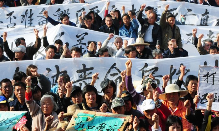 illagers hold banners and placards during a protest rally by residents of Wukan, a fishing village in the southern province of Guangdong, as they demand the government take action over illegal land grabs and the death in custody of a local leader on December 19, 2011. (STR/AFP/Getty Images)