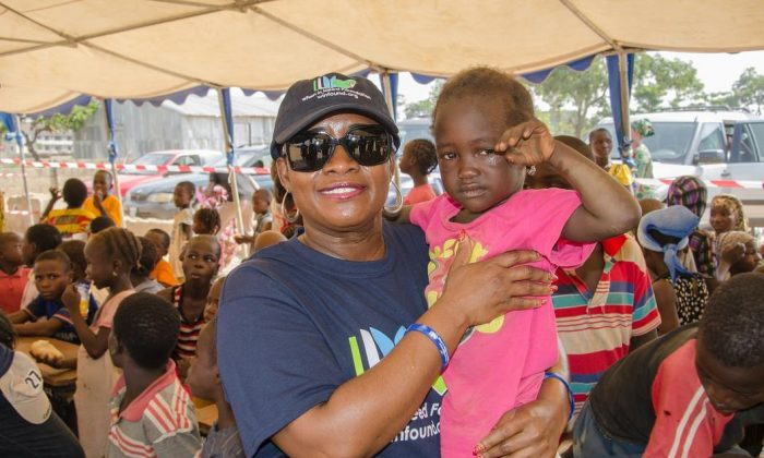 When In Need Foundation President Ms. Chetachi Ecton holds a child at the Kuchingoro IDP camp in the Galadimawa area of Abuja, Nigeria. (When In Need Foundation)