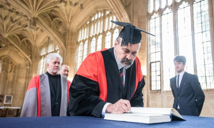 Monsignor Professor Tomáš Halík pauses to sign his name in the Honorary Degrees Book in the Divinity School, Oxford on June 22, 2016. Spanish film-maker, Mr Pedro Almodóvar and the Estonian composer Mr Arvo Pärt wait in line. Mr Almodóvar was awarded a Doctor of Letters while Mr Pärt was awarded a Doctor of Music. (John Cairns Photography)