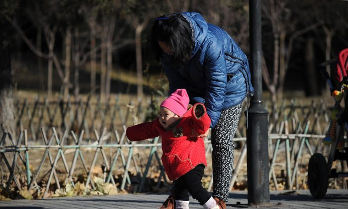 A woman and child walk at a park in Beijing on November 26, 2013. (Wang Zhao/AFP/Getty Images)