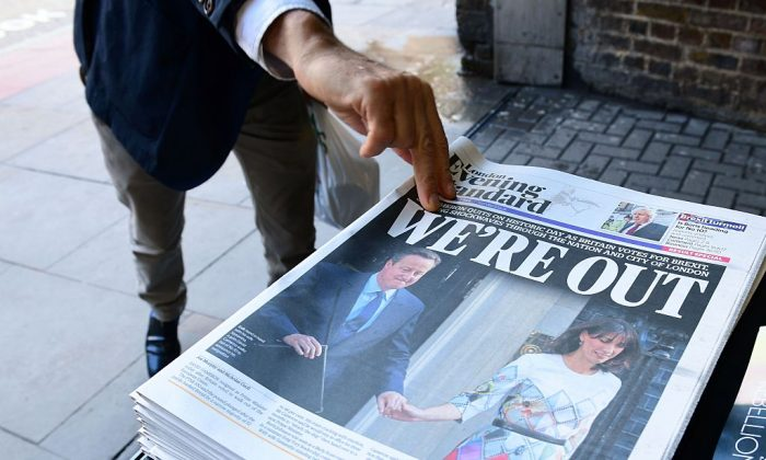 A man takes a copy of the London Evening Standard with the front page reporting the resignation of British Prime Minister David Cameron and the vote to leave the EU in a referendum, showing a pictured of Cameron holding hands with his wife Samantha as they come out from 10 Downing Street, in London on June 24, 2016.  (Leon Neal/AFP/Getty Images)