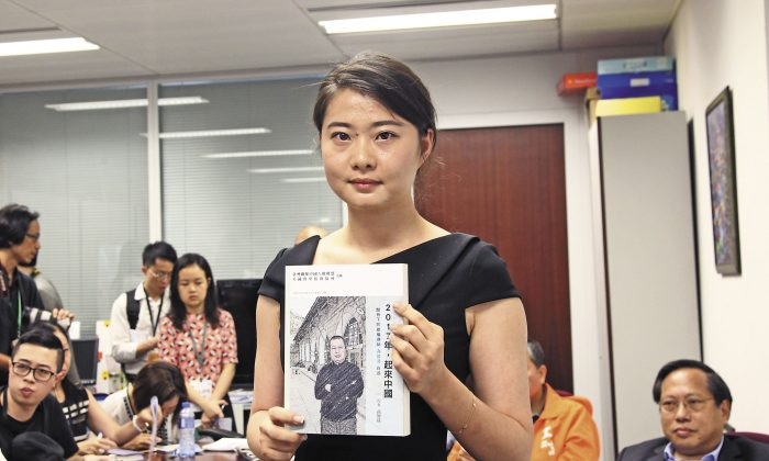 Grace Geng, Gao Zisheng's daughter, holds a copy of Gao's new book at the book launch ceremony, in  Hong Kong on June 16, 2016. (Stone Poon/Epoch Times)