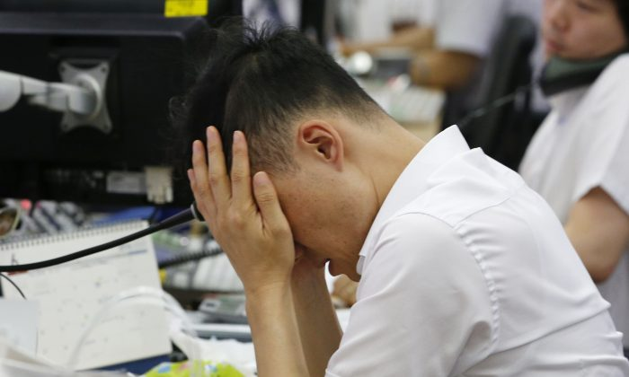 A currency trader rubs his eyes at the foreign exchange dealing room in Seoul, South Korea, Friday, June 24, 2016.  (AP Photo/Lee Jin-man)