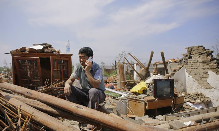 YANCHENG, CHINA - June 25:   A villager sitting in front of the collapsed house in Danping Village of Yancheng City,  Jiangsu Province. A total of 99 people were killed after severe storms in several towns in Jiangsu on June 23, 2016, with nearly 1,000 injured. (Photo by Wang He/Getty Images)