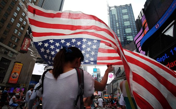 A tourist covers her head with a scarf made like a US flag as she walks under light rain in Times Square on July 4, 2015 in New York. ( JEWEL SAMAD/AFP/Getty Images)