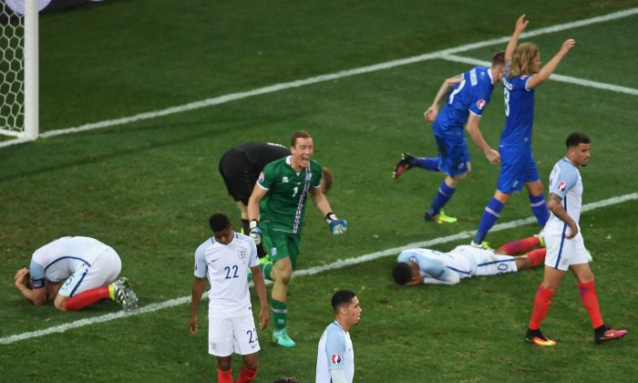 Gylfi Sigurdsson (No. 10) of Iceland falls to his knees in celebration as his team knocked out England at Euro 2016 on June 27, 2016 in Nice, France. (Laurence Griffiths/Getty Images)