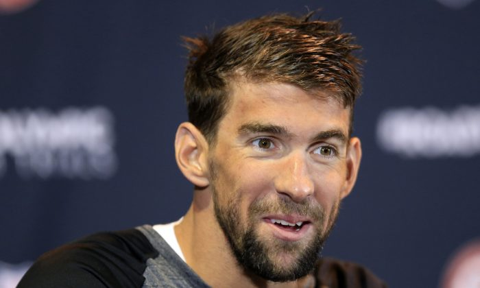 Michael Phelps, who's won 18 Olympic gold medals, is trying to pass on his knowledge to other swimmers as he prepares for his final Olympics. (AP Photo/Orlin Wagner)