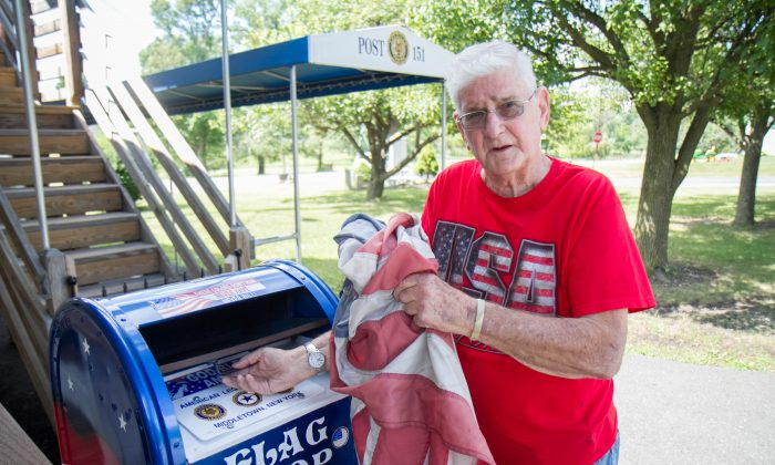 """Myron """"Bucky"""" Simpson next to the flag drop he set up at the American Legion in Middletown on June 29, 2016. (Holly Kellum/Epoch Times)"""