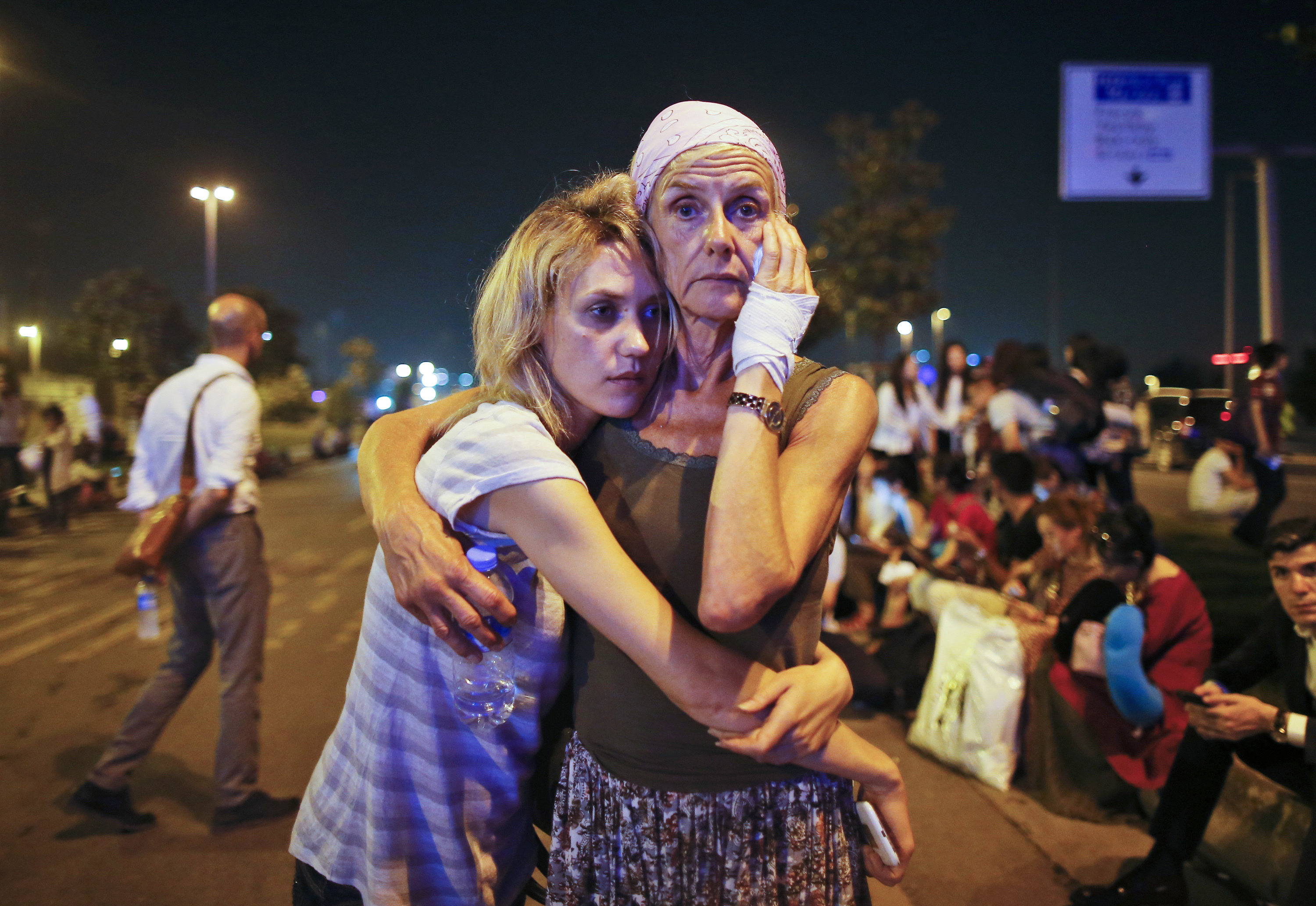 Passengers embrace each other as they wait outside Istanbul's Ataturk airport, early Wednesday, June 29, 2016 following their evacuation after a blast. Suspected Islamic State group extremists have hit the international terminal of Istanbul's Ataturk airport, killing dozens of people and wounding many others, Turkish officials said Tuesday. Turkish authorities have banned distribution of images relating to the Ataturk airport attack within Turkey. (AP Photo/Emrah Gurel) TURKEY OUT