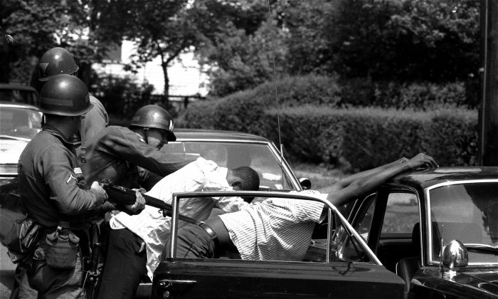 Blacks are searched at a bayonet point by National Guardsmen in Newark, New Jersey, July 17, 1967.  The National Guardsmen entered the riot-torn area of the city at daybreak and searched all cars leaving the riot zone.  A white policeman was shot and died after being beaten and stomped by a gang following the shooting of a 22 year old black man.  (AP Photo/Eddie Adams)