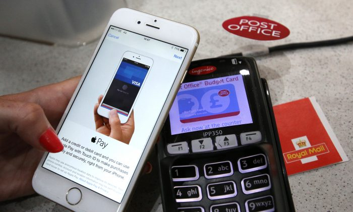 An iPhone is used to make an Apple Pay purchase at The Post Office in London, England, on July 14, 2015. (Peter Macdiarmid/Getty Images)