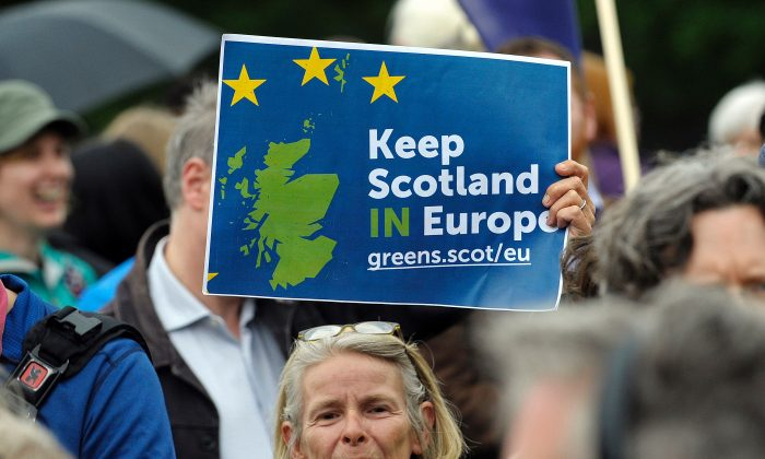 """A woman holds up a placard at a demonstration by Pro EU campaigners outside the Scottish Parliament ahead of a debate on the EU Referendum result and the implications for Scotland, in Edinburgh, Scotland on June 28, 2016. The Scottish National Party is weighing another referendum on Scotland separating from the U.K. after the """"leave"""" side won last week's Brexit referendum. (ANDY BUCHANAN/AFP/Getty)"""