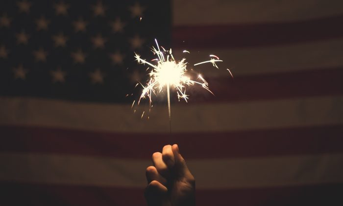 A file photo of a sparkler in front of a United States flag.  (Trent Yarnell/Unsplash.com)