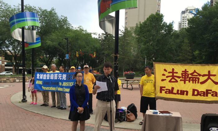 Jay Brauneisen, an Edmonton resident whose mother-in-law, Huixia Chen, has been detained in China for her practice of Falun Dafa, speaks at a rally calling for her release on June 30, 2016 in Edmonton, while his wife Hongyan Lu, Chen's daughter, looks on. (Omid Ghoreishi/Epoch Times)