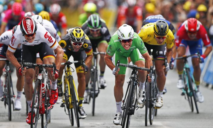 Dimension Data's Mark Cavendish, wearing the best sprinter's green jersey, crosses the finish line ahead Lotto-Soudal's Andre Greipel, left, and Peter Sagan of Tinkoff, wearing the overall leader's yellow jersey, to win Stage 3 of the Tour de Franc, 223.5 kilometers (138.6 miles) from Granville to Angers, France, Monday, July 4, 2016. (AP Photo/Peter Dejong)