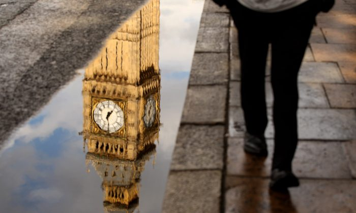 A man walks past a puddle with the reflection of Big Ben's Clock Tower in London, England, on July 14, 2010. (Oli Scarff/Getty Images)