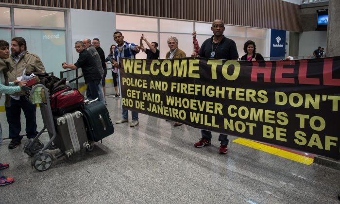 Police officers and firemen welcome passengers with a protest banner at the Tom Jobim International Airport in Rio de Janeiro on July 4. (Vanderlei Almeida/AFP/Getty Images)