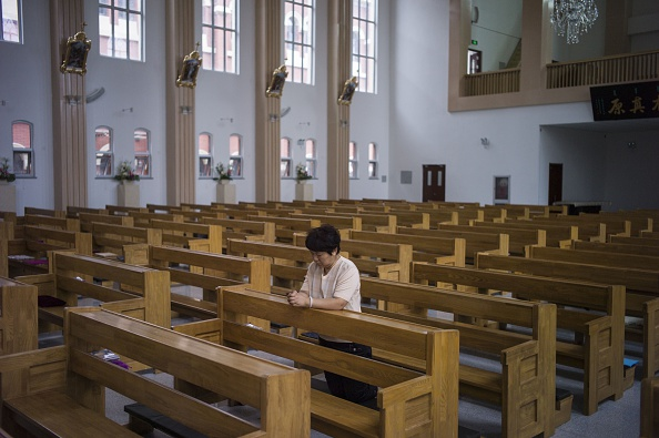 A woman prays at a Catholic church in Tianjin on June 7, 2015. Many churches in China's province of Zhejiang have been turned into cultural centers. (Fred Dufour/AFP/Getty Images)