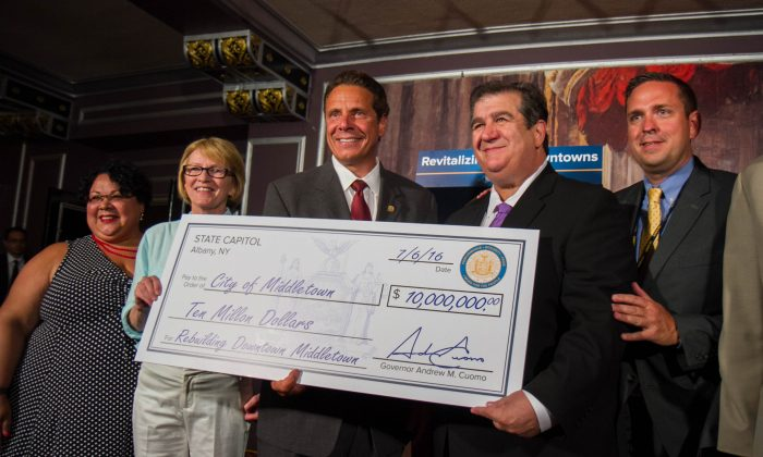 (L-R) New York Secretary of State Rossana Rosado, New York Assemblywoman Aileen Gunther, New York Governor Andrew Cuomo, Middletown Mayor Joseph DeStefano, and Orange County Executive Steven Neuhaus holding a check for the state's $10 million Downtown Revitalization Initiative grant to Middletown at the Paramount Theatre in Middletown on July 6, 2016. (Holly Kellum/Epoch Times)