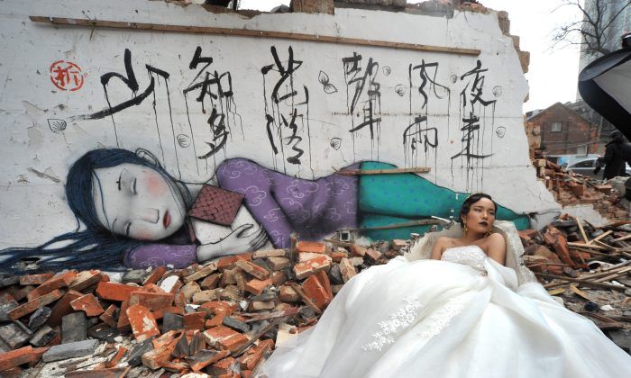 A bride poses for wedding photos before a graffiti mural on Kangding Road where old houses are demolished on January 22, 2015 in Shanghai. (VCG/VCG via Getty Images)