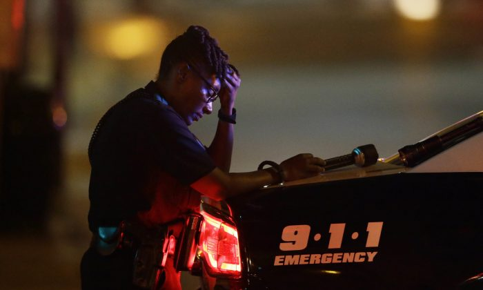 A Dallas police officer, who did not want to be identified, takes a moment as she guards an intersection in the early morning after a shooting in downtown Dallas, Friday, July 8, 2016. At least two snipers opened fire on police officers during protests in Dallas on Thursday night; some of the officers were killed, police said. (AP Photo/LM Otero)