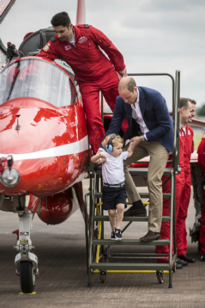 Prince George is lifted down from the cockpit of a red arrows aircraft as his father Prince William, Duke of Cambridge looks on during a visit to the Royal International Air Tattoo at RAF Fairford on July 8, 2016 in Fairford, England. (Photo by Richard Pohle - WPA Pool/Getty Images)