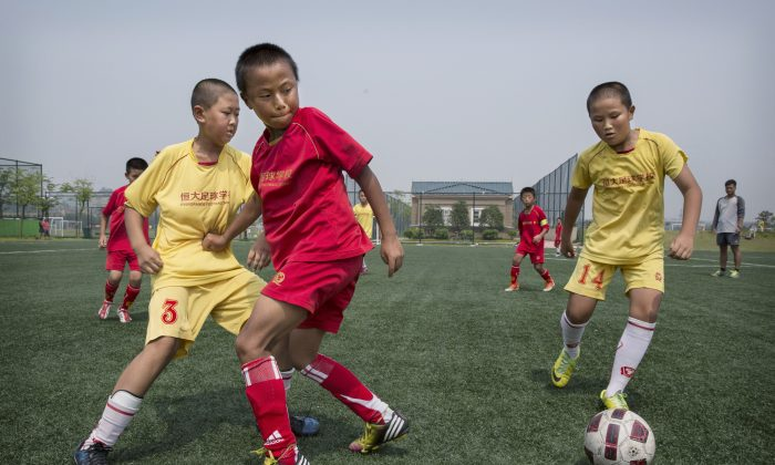 Children play soccer on a practice pitch at the Evergrande International Football School in Guangdong Province, China. China aims to build more than 20,000 soccer schools to raise its international standing in the sport of soccer. (Kevin Frayer/Getty Images)