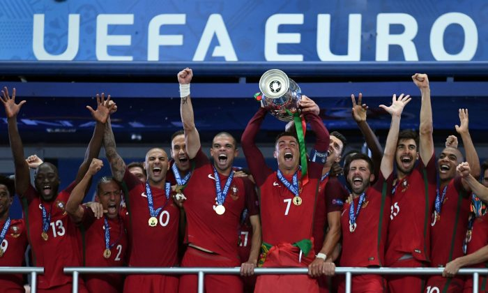 Cristiano Ronaldo lifts the Henri Delaunay Cup as he celebrates with his Portuguese teammates after they won the Euro 2016 final against France at the Stade de France in Saint-Denis on July 10, 2016. (Francisco Leong/AFP/Getty Images)