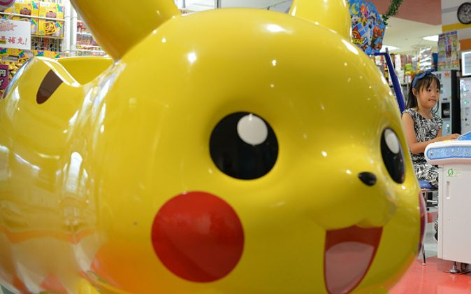 A Japanese girl plays at a Pokemon series character Pikachu-designed vehicle in Tokyo, Japan, July 12, 2016. New mobile game Pokemon Go has become an overnight sensation with U.S. (Photo by Hitoshi Yamada/NurPhoto via Getty Images)