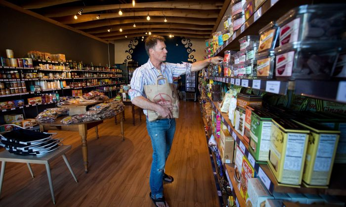 Pirate Joe's owner Michael Hallatt stocks the shelves at his Vancouver store where he resells products from the U.S. specialty grocery store Trader Joe's, Aug. 21, 2013. Hallatt has been crossing the border and buying products from the stores and reselling them since January 2012. (THE CANADIAN PRESS/Darryl Dyck)