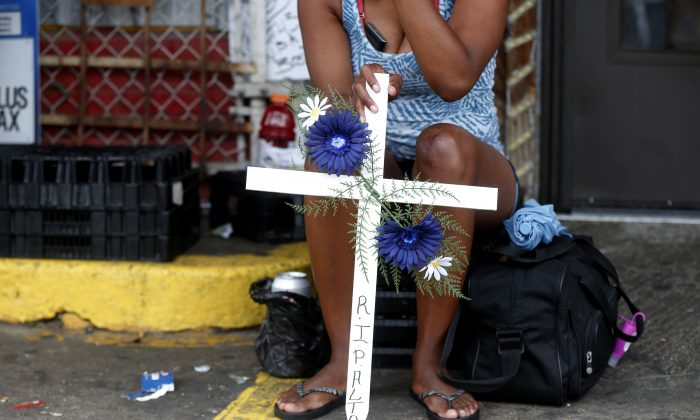 Sepia Greene, of Baton Rouge, La., holds a crucifix in memory of Alton Sterling outside the Triple S Food mart in Baton Rouge, La., Monday, July 11, 2016. Sterling was shot and killed last Tuesday by Baton Rouge police while selling CD's outside the convenience store. (AP Photo/Gerald Herbert)