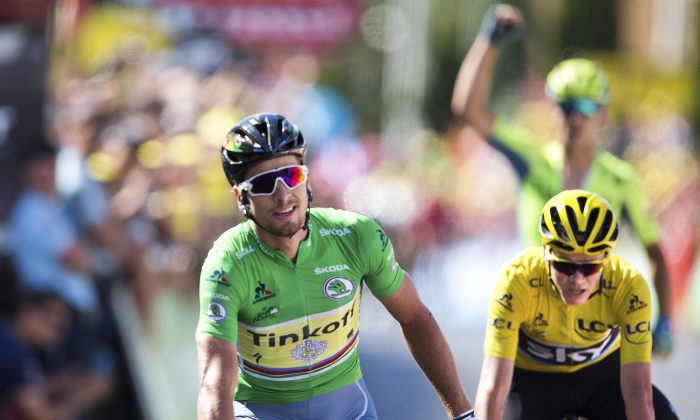 Tinkoff's Peter Sagan crosses the finish line ahead of Sky's Chris Froome, while Tinkoff's Maciej Bodnar, rear, fist-pumps at the end of Stage 11 of the 2016 Tour de Franc, 162.5 kilometers (100.7 miles) from Carcassonne to Montpellier, France, Wednesday, July 13, 2016.