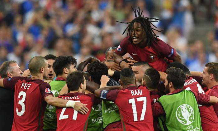 Renato Sanches (top) and Portugal players celebrate their team's first goal scored by Eder (obscured) during the UEFA EURO 2016 Final match between Portugal and France at Stade de France on July 10 in Paris, France. (Laurence Griffiths/Getty Images)