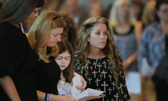 Heidi Smith, second from left, stands between her daughters, Victoria, left, and Caroline Smith, center, with Dallas Sr. Cpl. Marcie St. John, right, standing nearby during the funeral for her husband, Dallas police Sgt. Michael Smith, at the Mary Immaculate Catholic Church in Farmers Branch, Texas, Wednesday, July 13, 2016. (Andy Jacobsohn/The Dallas Morning News via AP)