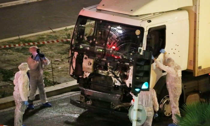 Authorities investigate a truck after it plowed through Bastille Day revelers in the French resort city of Nice, France, Thursday, July 14, 2016.  (Sasha Goldsmith via AP)